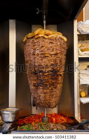 A large piece of dark lamb mutton meat layered under fat cooking in a stainless steel grill machine often found in and outside of shawarma and kebab restaurants of the Middle East