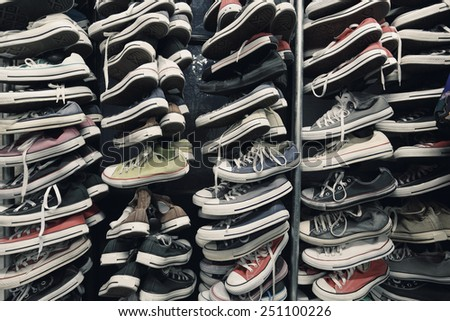 A large pile of old worn sneakers, shoes - stock photo