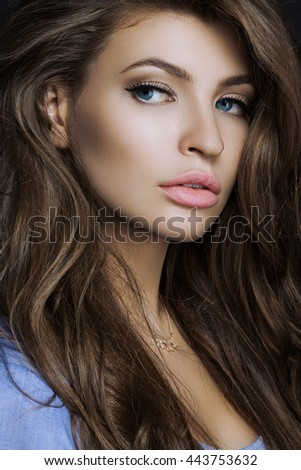 a large portrait of a sexy and beautiful girl with a professional styling and a make up on black background. girl looking at the camera.big lips
