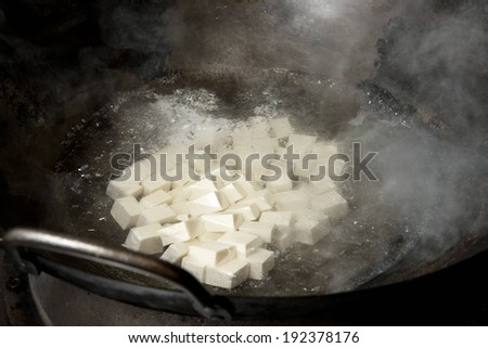 A large pot with handles boiling some food. - stock photo