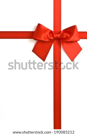 A large present in a white box wrapped with a big red bow. - stock photo