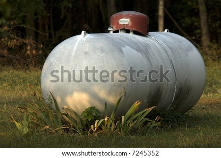 A large propane gas tank with plants growing around it. - stock photo