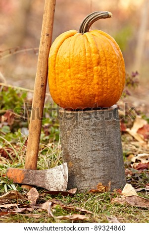 A large pumpkin on a log outdoor in the grass