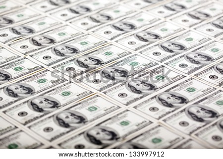 A large quantity of 100 US$ money notes lined up in a vertical row. Very shallow depth of field.