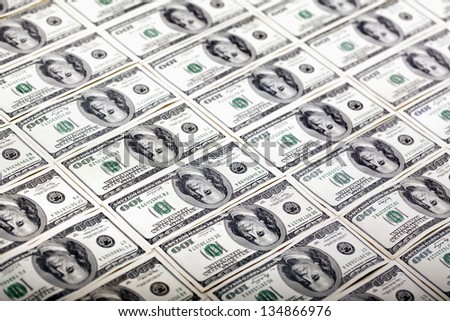 A large quantity of 100 US$ money notes lined up in rows. Shallow depth of field. - stock photo