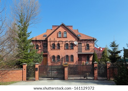 A large red brick built country house with a tiled roof