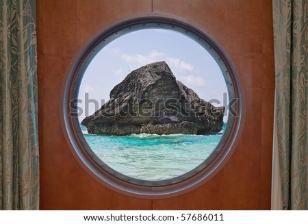 A large rock in the atlantic ocean in the coastal waters of Bermuda seen through the porthole of a cruise ship. The scene is from Horseshoe Bay in Bermuda. - stock photo
