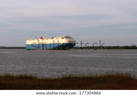 A large ship or barge built specifically for transporting automobiles leaves port near Brunswick Georgia - stock photo