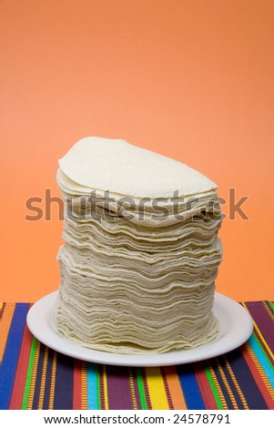 A large stack of corn tortillas on a plate. Colorful orange, textured paper background. Colorful textured fabric tablecloth.