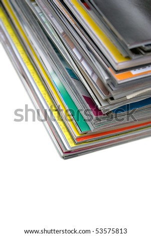A large stack of magazines piled high isolated over white with copyspace.  Shallow depth of field. - stock photo