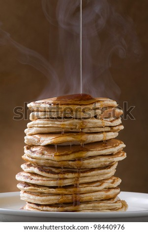 A large stack of steaming pancakes on a white plate with syrup being poured and dripping down the sides on a golden brown background - stock photo