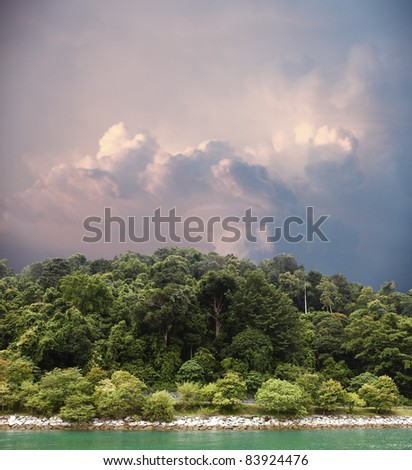 A large surreal storm cloud catching the evening sunlight looming across the horizon of a coastal green forest hill. - stock photo