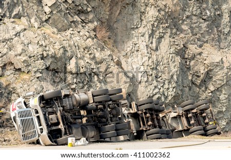 A large tanker truck flipped on its side in a ditch. The truck has 30 wheels, and the front appears damaged. A high cliff is in the background. Room for text. - stock photo
