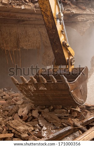 A large track hoe excavator tearing down an old house for Old house tracks