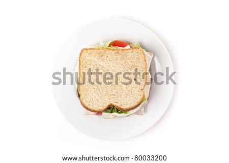 A large turkey sandwich with tomatoes, cheese, and lettuce - stock photo