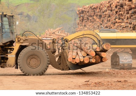 A large wheeled front end log loader and track hoe working the log yard at a lumber processing mill that specializes in small logs - stock photo