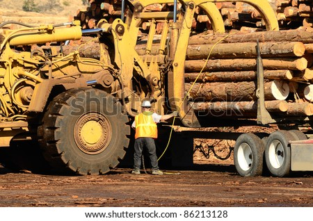 A large wheeled loader unloads a log truck at a small log sawmill in Oregon - stock photo