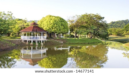 A large white gazebo reflected in the surface of a lake - stock photo