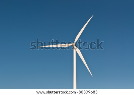 A large wind turbine spins with a deep blue sky in the background.