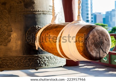 A large wooden ram hangs still beside an enormous iron bell at Bongeunsa Temple in Seoul, South Korea. - stock photo