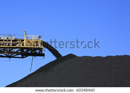 a large yellow conveyor belt carrying coal and emptying onto a huge pile. - stock photo