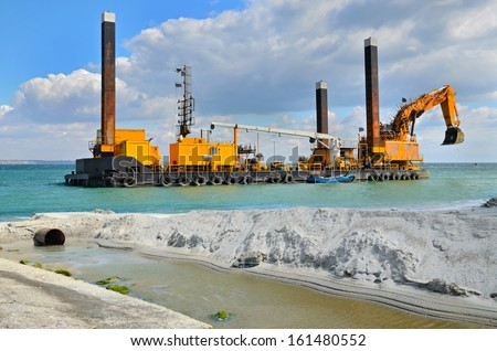 A large yellow excavator machine construct sea defences on the beach - stock photo