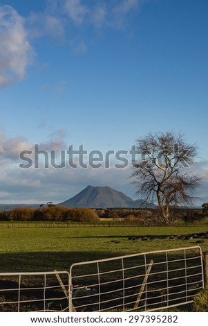 A late-afternoon, winter view of Mount Edgecumbe, a volcano in the Bay of Plenty, New Zealand. The stretch of farmland and the dramatic sky is a feast to bold. Good for greeting cards and other ideas. - stock photo