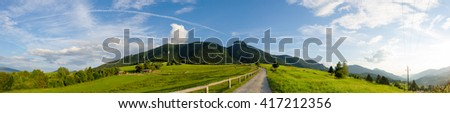 A late summer evening panoramic view of a rural sheep farm on a top of a mountain pass with dust country road / field path with a wooden cottages, enclosure, hills, blue cloudy sky. - stock photo