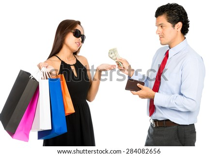 A latino husband gives more cash to his demanding superficial Asian wife holding shopping bags and wearing stylish clothes extending her hand out.