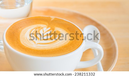 A Latte Coffee art in the white cup on the wooden desk. - stock photo