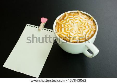 A Latte Coffee art on the black desk. - stock photo