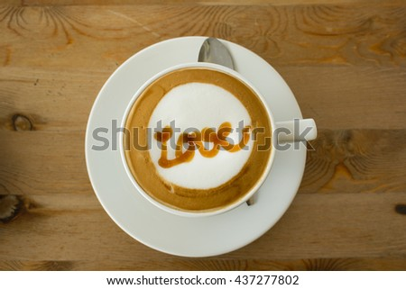 """A Latte Coffee art on the wooden desk.A cup of coffee Art with """"Love"""" word. - stock photo"""