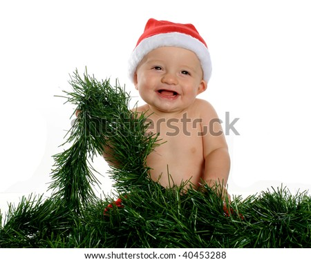 A laughing baby in red pants and Santa hat, playing with green Christmas garland.  Isolated on white. - stock photo