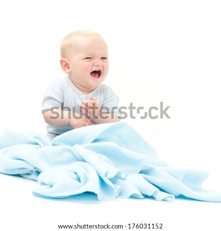 A laughing baby is sitting on a blue blanket. - stock photo