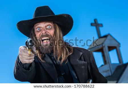 A laughing cowboy holding a gun near a church - stock photo