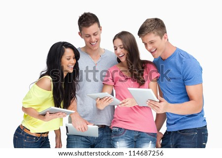A laughing group of friends looking at their tablets while beside one another