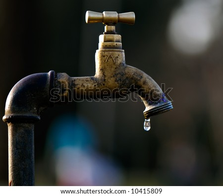 A leaky tap is wasting water - stock photo
