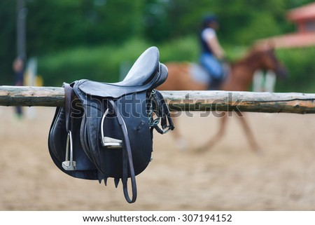 A leather saddles horse in a stable at the summer time - stock photo