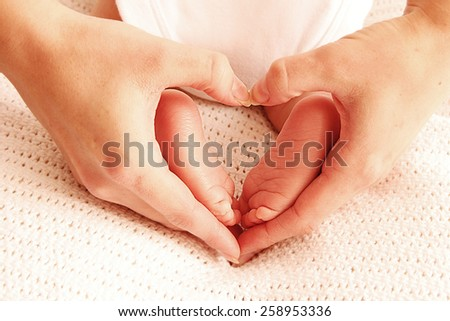 a leg cute newborn little baby in mother's hands  - stock photo