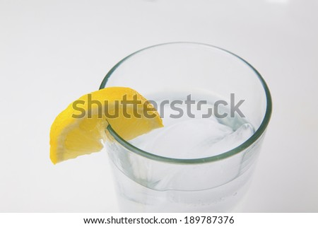 A lemon on a glass of water.