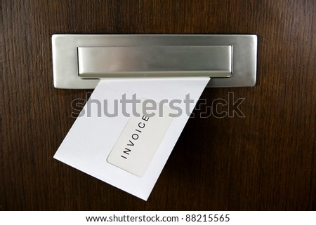 A letter in a letter box of a door with written INVOICE - stock photo