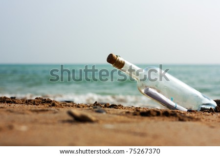 A Letter or message in a bottle on the shore,cast out by ocean or sea - stock photo