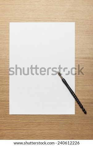 A letter paper and fountain pen on the wood desk(table), top view at the studio. - stock photo