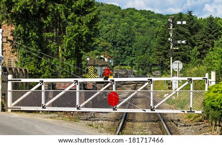 A level crossing gate on a country rail track. - stock photo