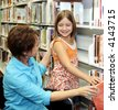 A librarian helps a child choose a book.  Shallow depth of field with focus on the little girl. - stock photo