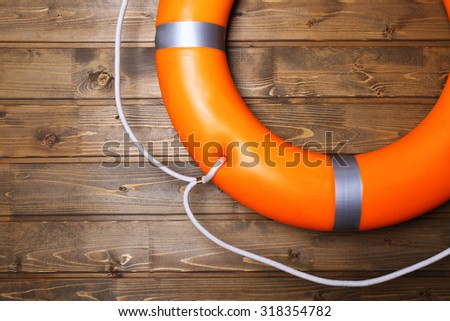 A life buoy on wooden wall - stock photo