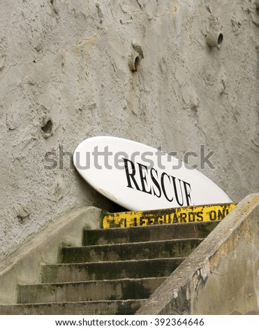 A life guard's rescue surfboard  leans against a concrete wall at the top of a stairway in preparation for a water rescue. - stock photo