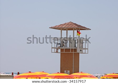 A life guard tower anong the umbrellas on the beach of Larnaca, Cyprus