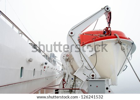A Lifeboat on a passenger cruise ship hangs ready to launch in foggy weather. - stock photo