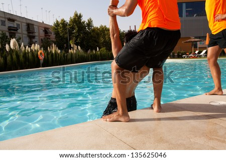 A lifeguard takes out a drowned man from a swimming pool. - stock photo